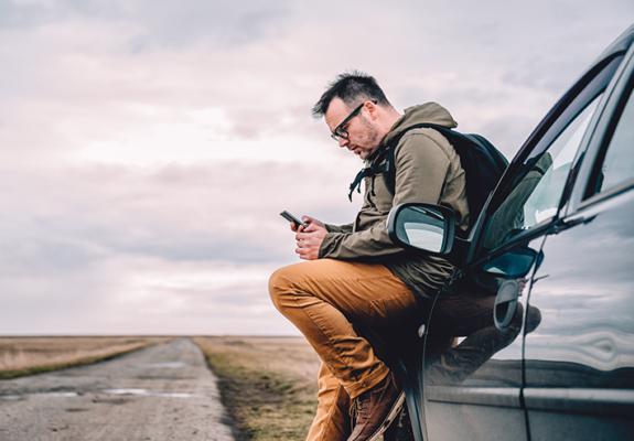 man texting his auto insurance